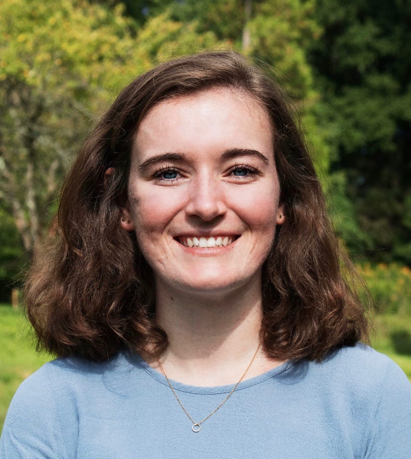 Annie Connolly-Sporing '20, wearing a blue shirt, stands in front of a background of trees.