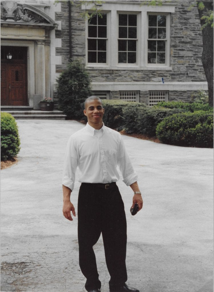 Kevin R. jones wears a white button-down shirt and black pants and stands in front of Sharpless Hall on his graduation day.
