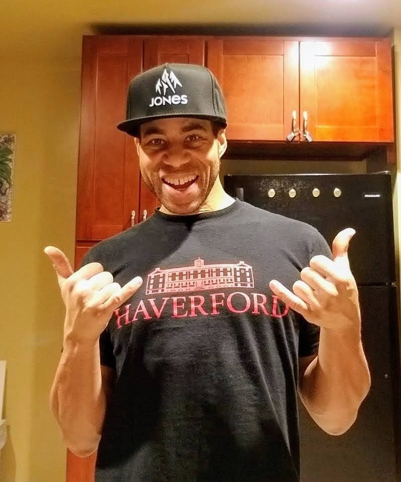 """Kevin R. Jones wearing a Haverford hat and t-shirt gives the """"hang loose"""" sign with both hands."""