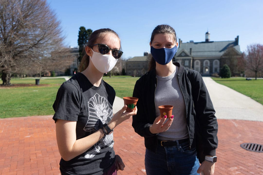 Two students in masks stand on Founders Green holding plants