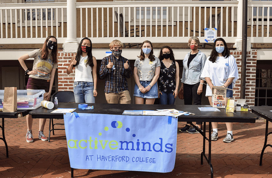 Students and President Wendy Raymond, all wearing masks, stand behind a table with an Active Minds banner on it in front of Founders Hall