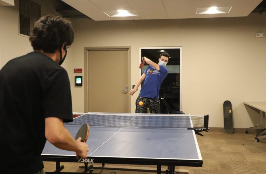 A student his a ping pong ball to another student, who crouches ready to hit it back.