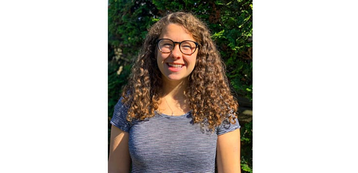 Emily Shutman '20 wears glasses and a striped t-shirt in this portrait