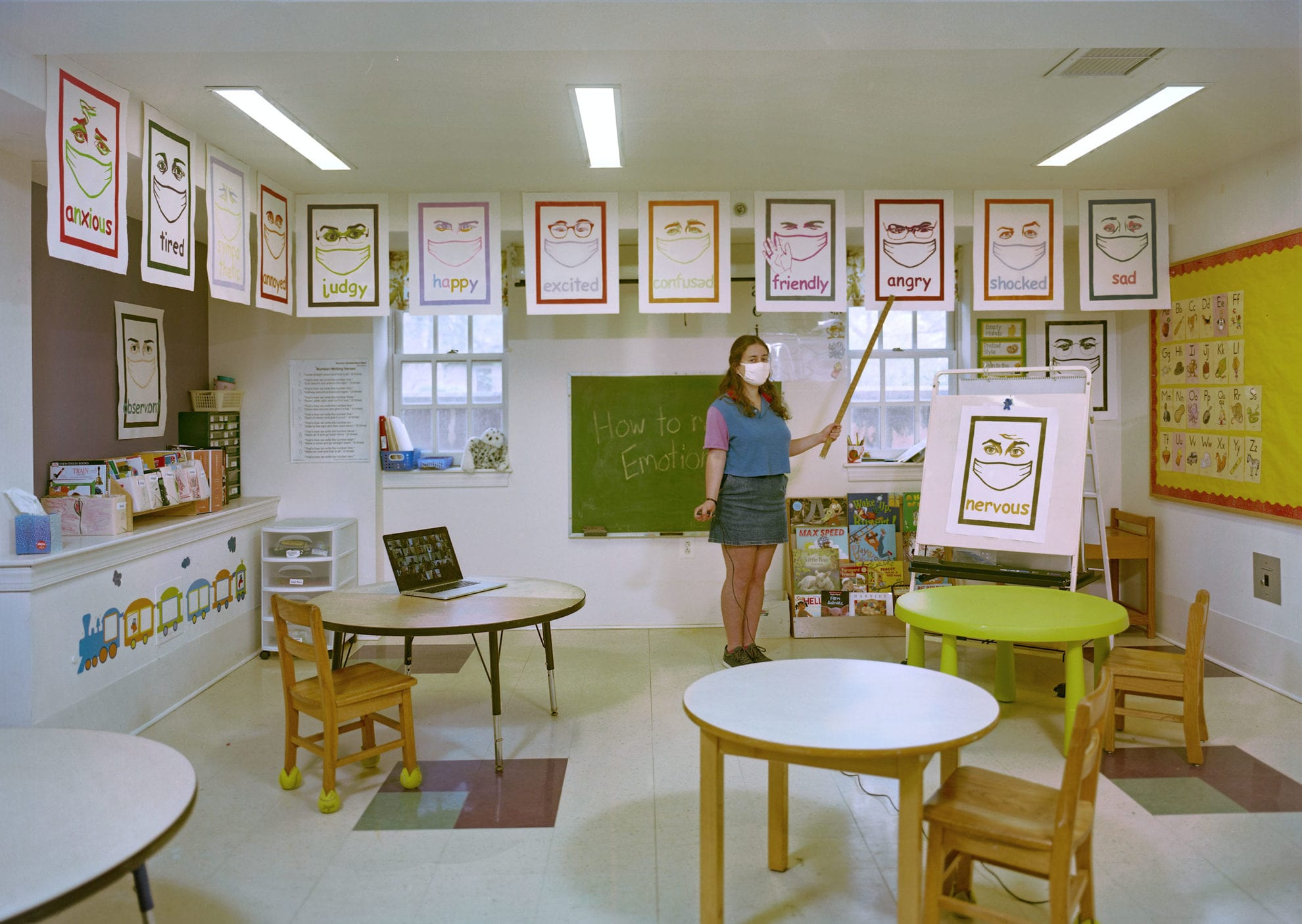 Rachel Grand BMC '21 stands in a classroom in the Phebe Thorne Anna School, showcasing some prints depicting various emotions.