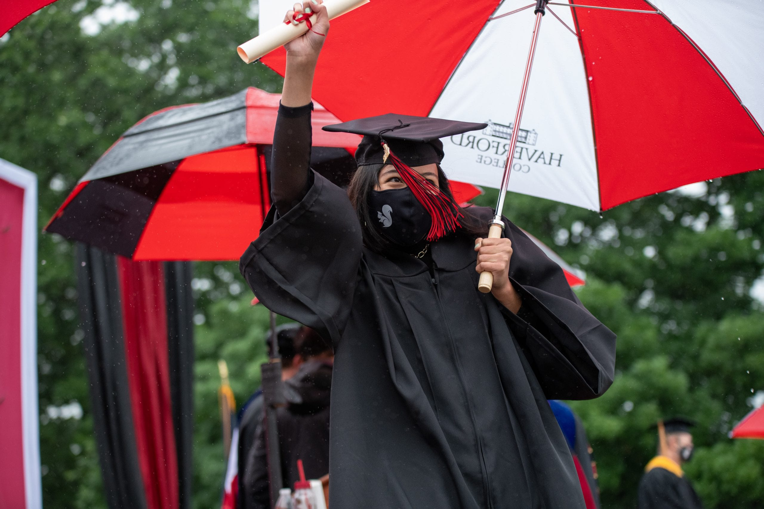 A graudate in a squirrel mask and black cap and gown holds a Haverford umbrella in one hand and her diploma in the other.