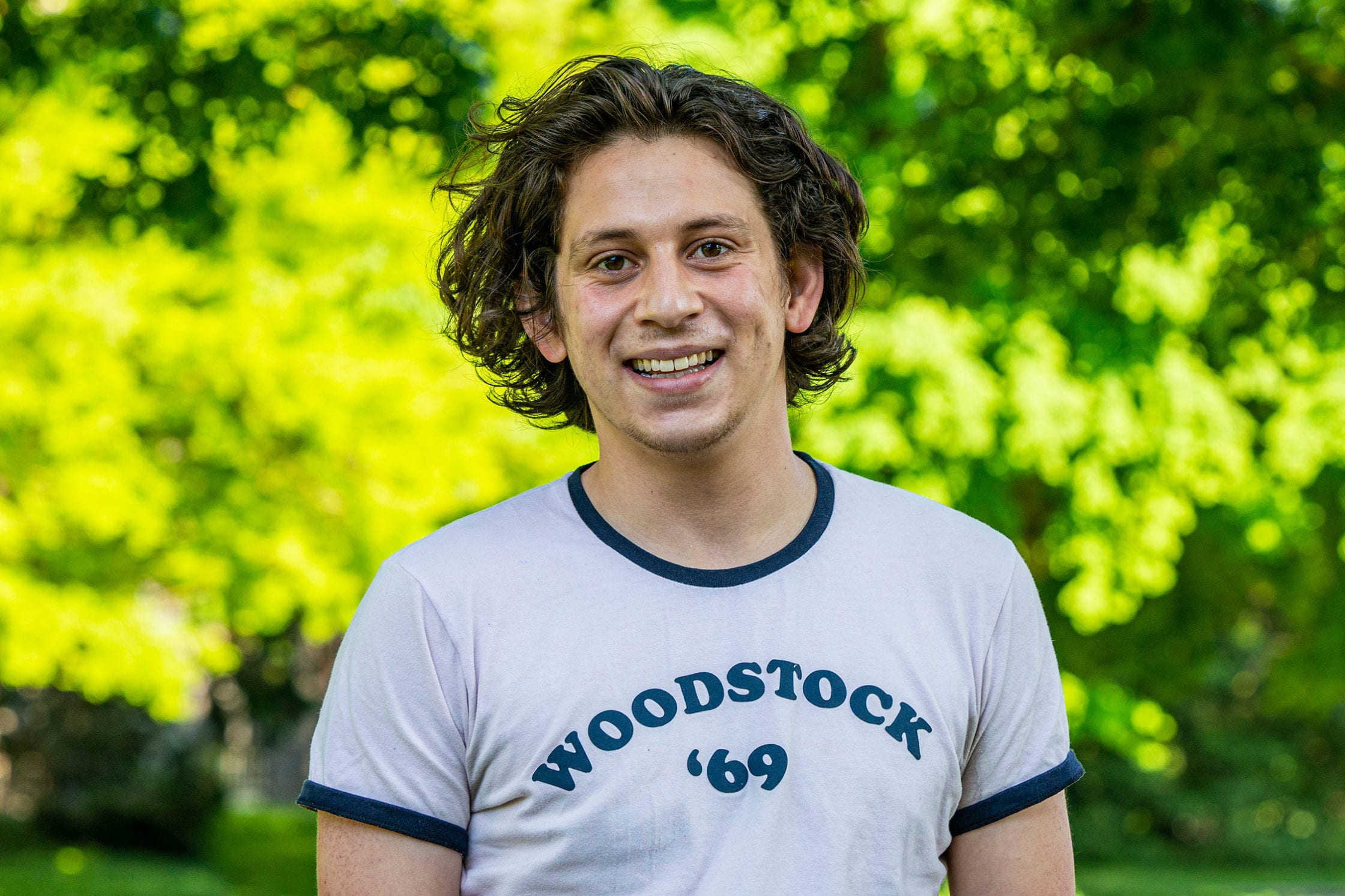 """Headshot of Federico wearing white shirt with """"Woodstock '69"""" in blue writing on it."""