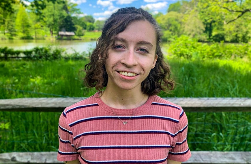 Headshot of Grace wearing a striped pink shirt in front of the duck pond.