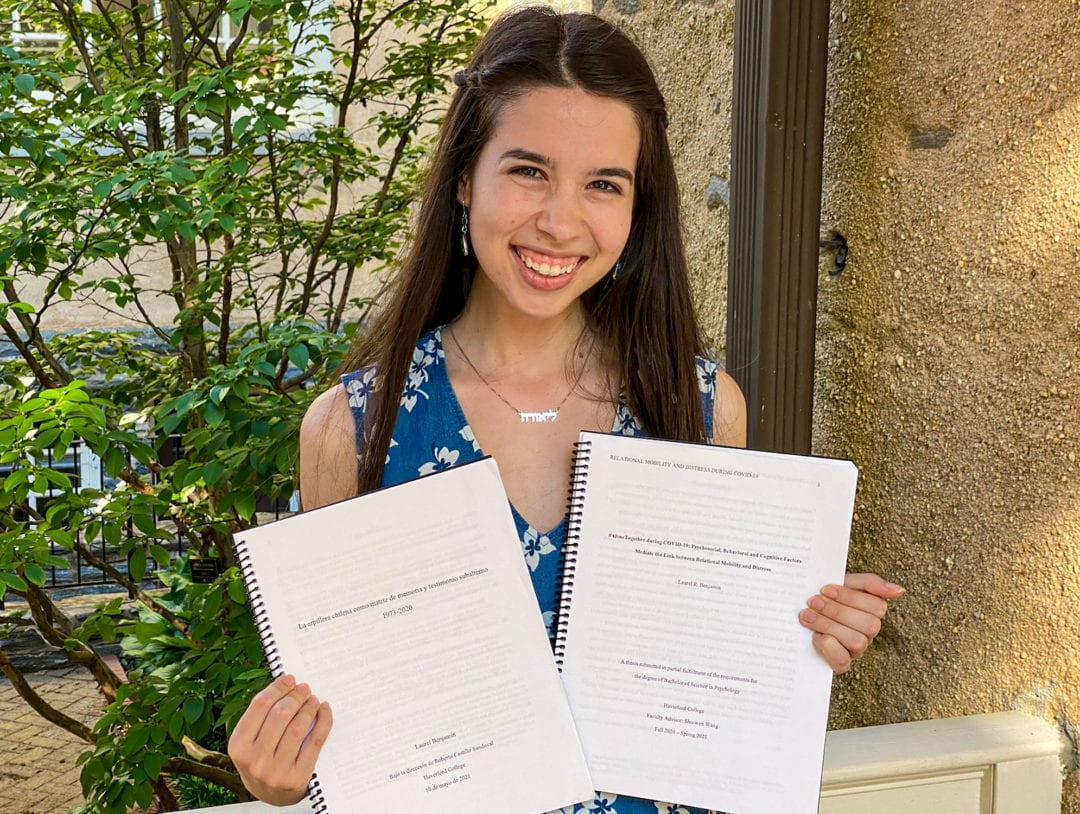 Photo of Benjamin holding her two theses in Founders courtyard.