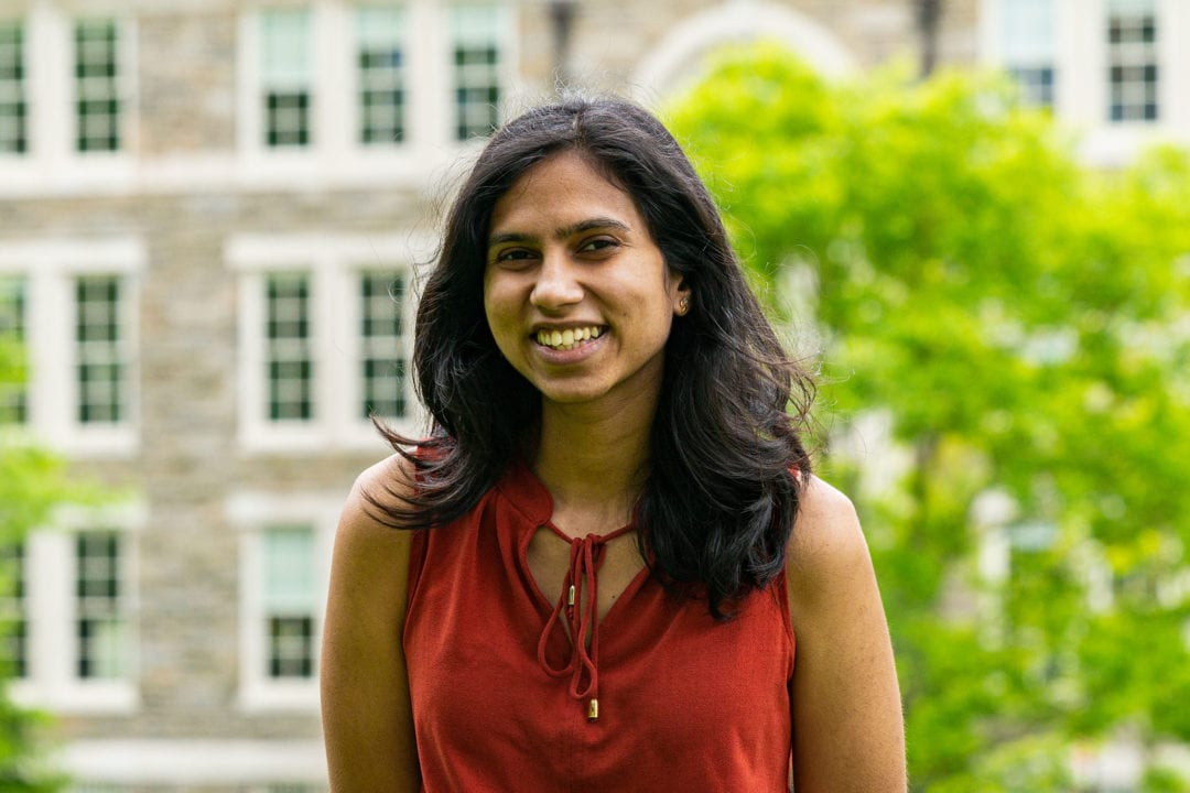 Headshot of Shreya in a red shirt standing in front of the KINSC.