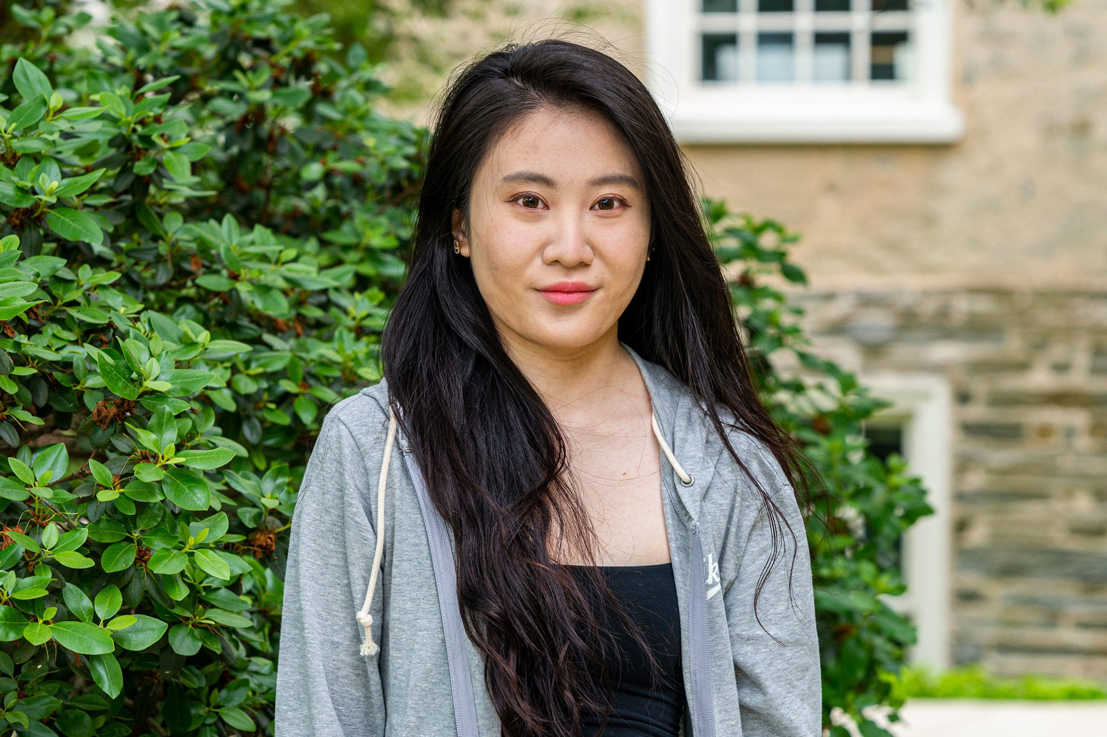 Headshot of Anqi standing to the side of Founders Hall.