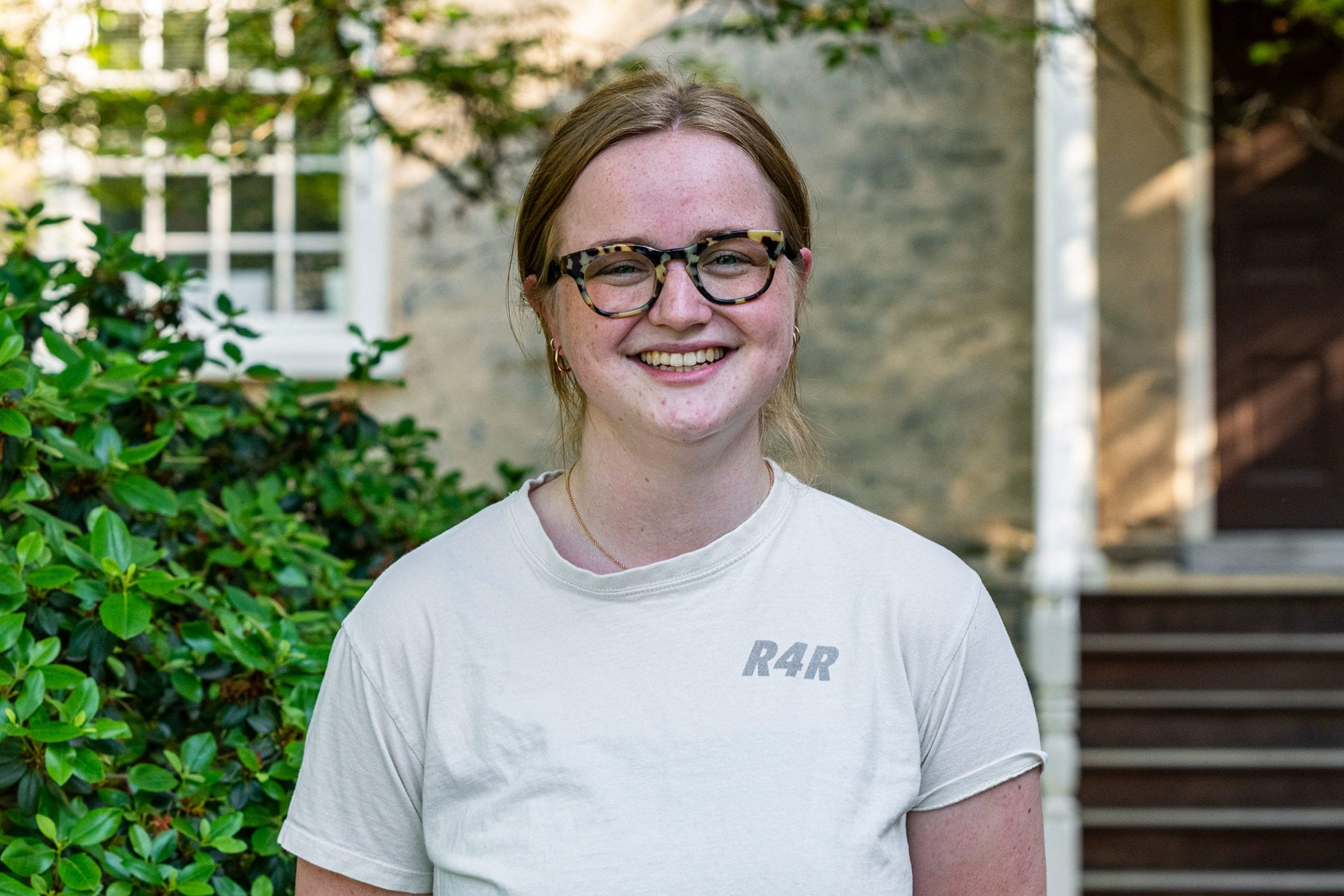 A headshot of Fiona wearing a white short-sleeved shirt standing in front of Founders Hall.