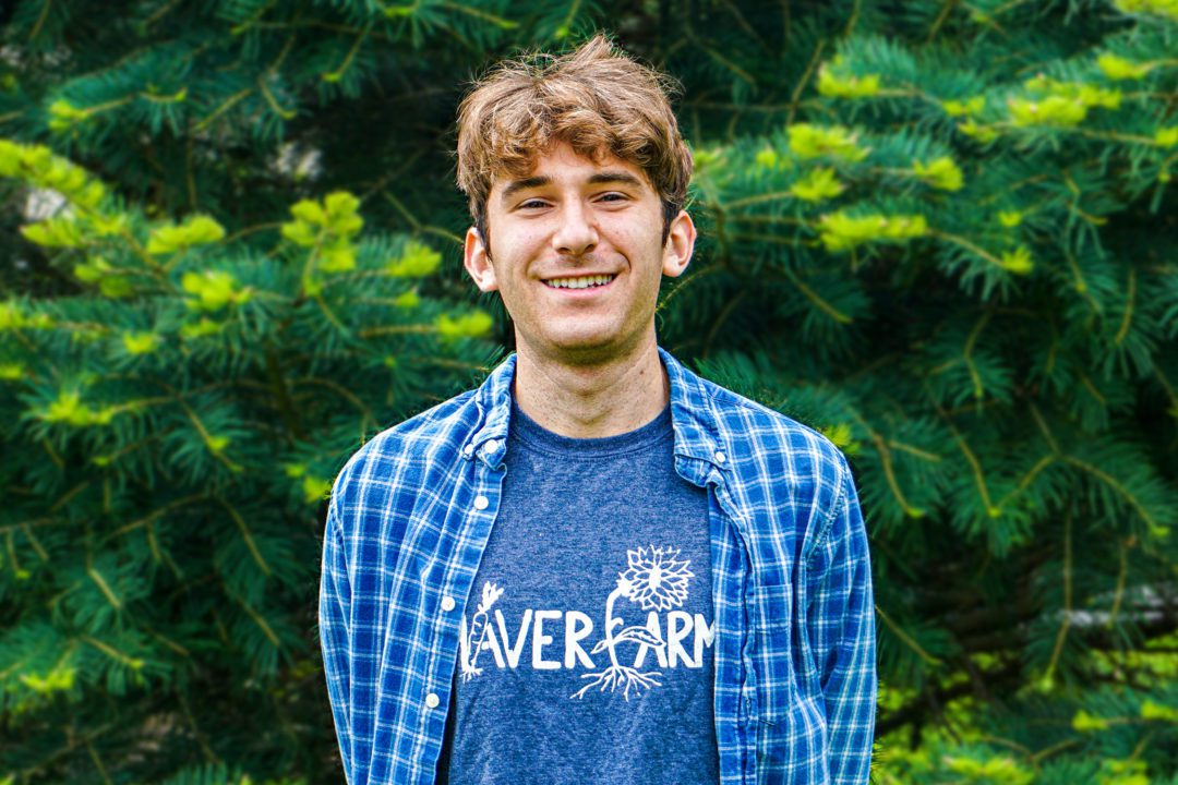 A photo of Jacob in front of a tree, wearing a blue Haverfarm shirt.