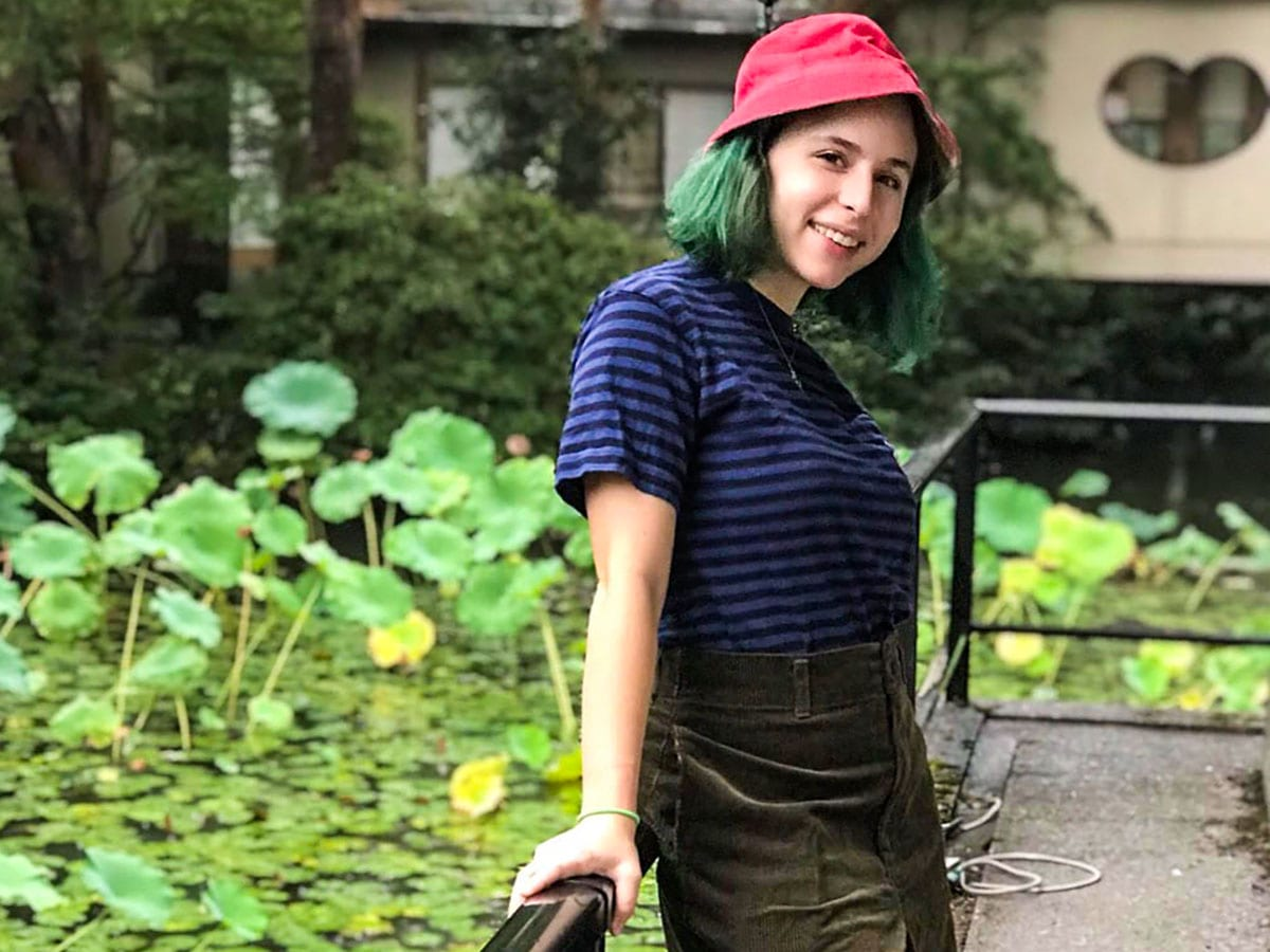 Sophie wearing a casual outfit smiling on a platform looking over a lilypad covered pond.