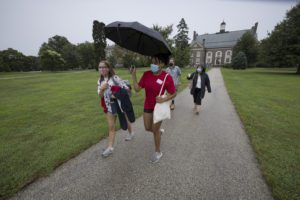 A student in a Chesick Scholar t-shirt holds an umbrella over another student with parents walking behind them.