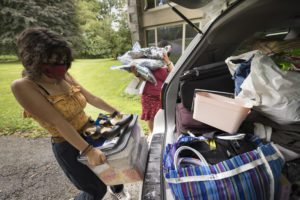 A masked student lifts boxes and shoes out of a trunk of a car.