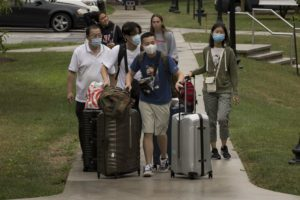 A masked student and his family wheel suitcases along the path