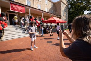 A parent takes a photo of her student in front of Founders Hall on Move-In Day