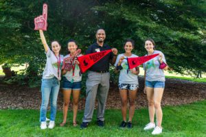 Dean John McKnight poses on Founders Green with four orientation leaders, each holding a Haverford banner or foam finger.