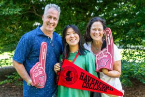 A student poses with her parents and red Haverford foam fingers and a Haverford banner