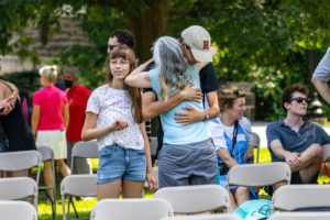A son in a Haverford hat hugs his mom.