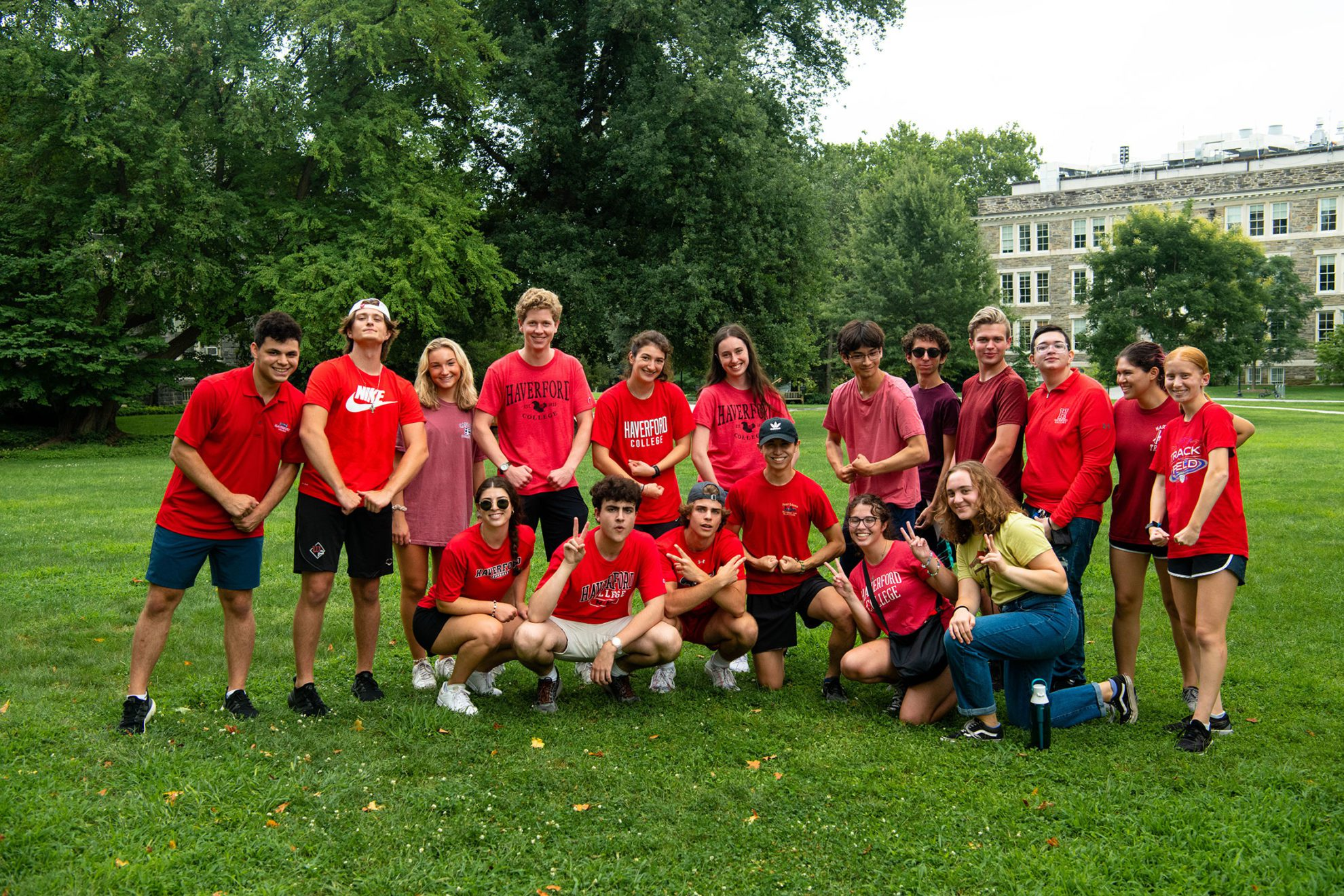 """A group of students in red t-shirts, many reading """"Haverford"""" across the front, pose on Founders Green."""