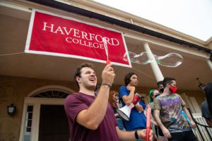 A student blowing bubbles under a Haverford College banner