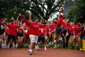 Members of the Red Fords, dressed in red shirts, jump and cheer.