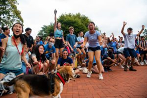 Peanut the dog stands in front of the cheering blue team.