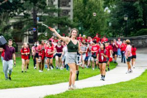 A student uses a bubble wand as the red team enters Founders Green, wearing red shirts.