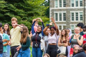Students cheering at Dorm Olympics and one makes a heart gesture with her hands.