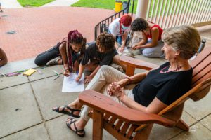 Students sitting on Founders Porch in front of Wendy Raymond, sketching her.