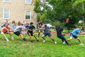The green team pulls at tug of war in front of Founders.