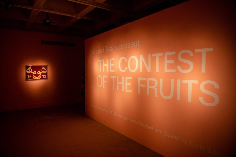 """A spotlight on a salmon-colored wall with a sign reading """"The Contest of the Fruits"""""""
