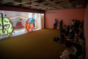 People gather in the gallery to watch the film. A pear and an apple are animated on the screen.