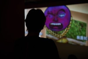 An animation of a plumb wearing a gold chain is projected on a screen. A silhouette of a person is in front of the screen.