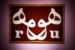 A maroon sign with white Uygher lettering on it.