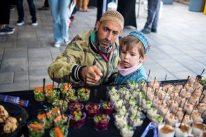 Payam Sharifi and his son look over the snack table at the opening reception outside Whitehead Campus Center.