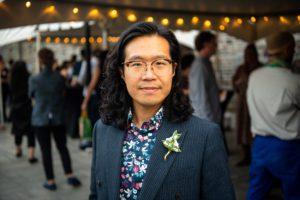 Professor Guangtian Ha wears glasses, a floral shirt, and a flower pin on the lapel of his jacket as he stands outside the reception tent.