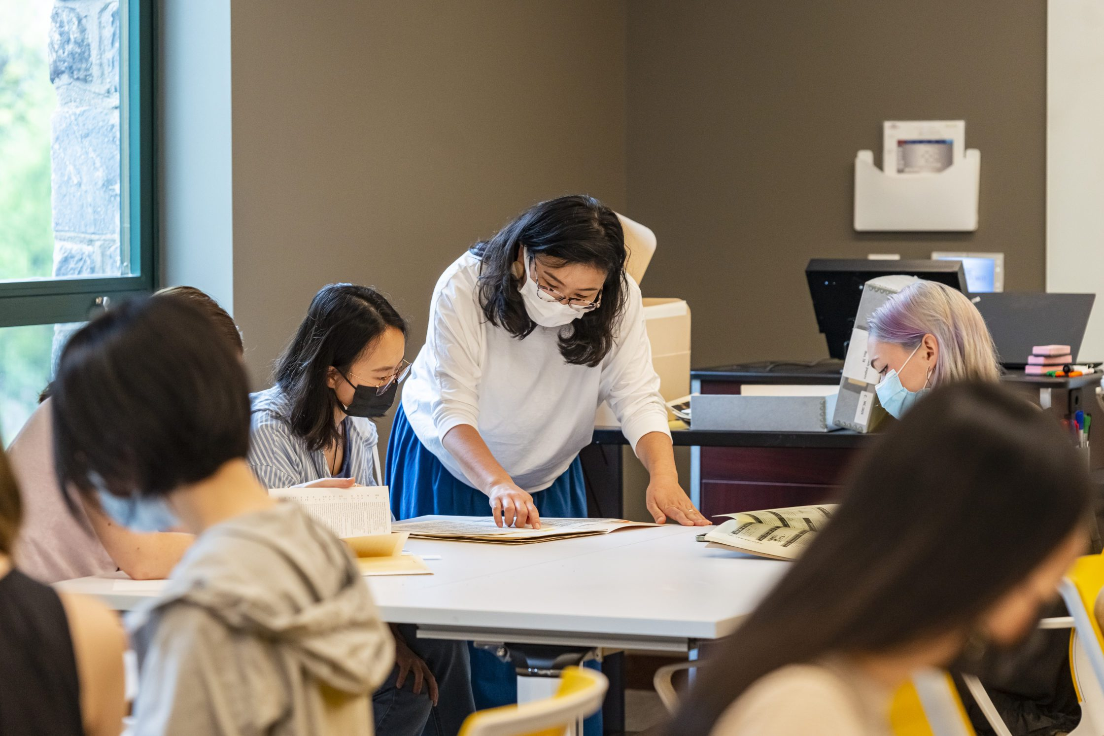 Kimiko Suzuki bends over a table in Lutnick Library going over documents with two masked students