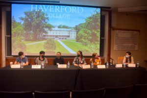Six student panelists sit at a table set for seven student speakers in front of a screen with an image of Founders Hall and the words Haverford College on it