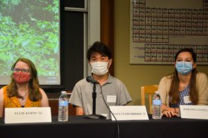 Three student panelists, all wearing masks, sit at a table in front of their name tags