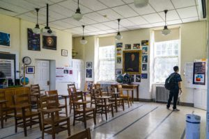 A classroom in the observatory covered in posters and a student looking at them