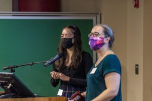 Bianca Teves and Karen Masters both wear masks and stand at the podium