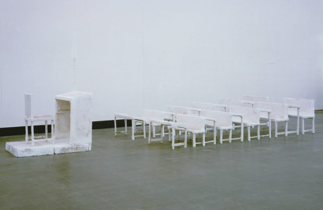 """Inge Mahn's sculpture """"Schulklasse,"""" which shows white rows of seating in front of a white teacher's podium"""