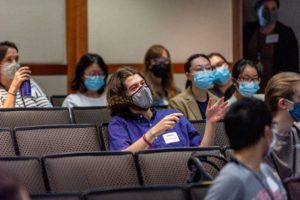 A student in a purple shirt and mask asks a question from the audience