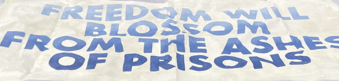 """A protest sign that reads """"Freedom Will Blossom From The Ashes Of Prisons"""""""