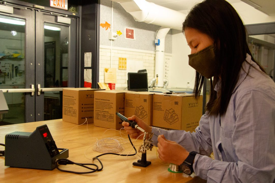 A masked student works on soldering in at a long table in the Maker Arts Space.
