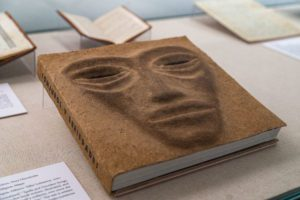 A book with a three-dimensional mask of a face on its cover in a glass display case.