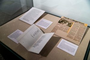 A glass display case with a literary magazine, a letter, and a Bi-Co News article related to the 1993 protests for racial justice.
