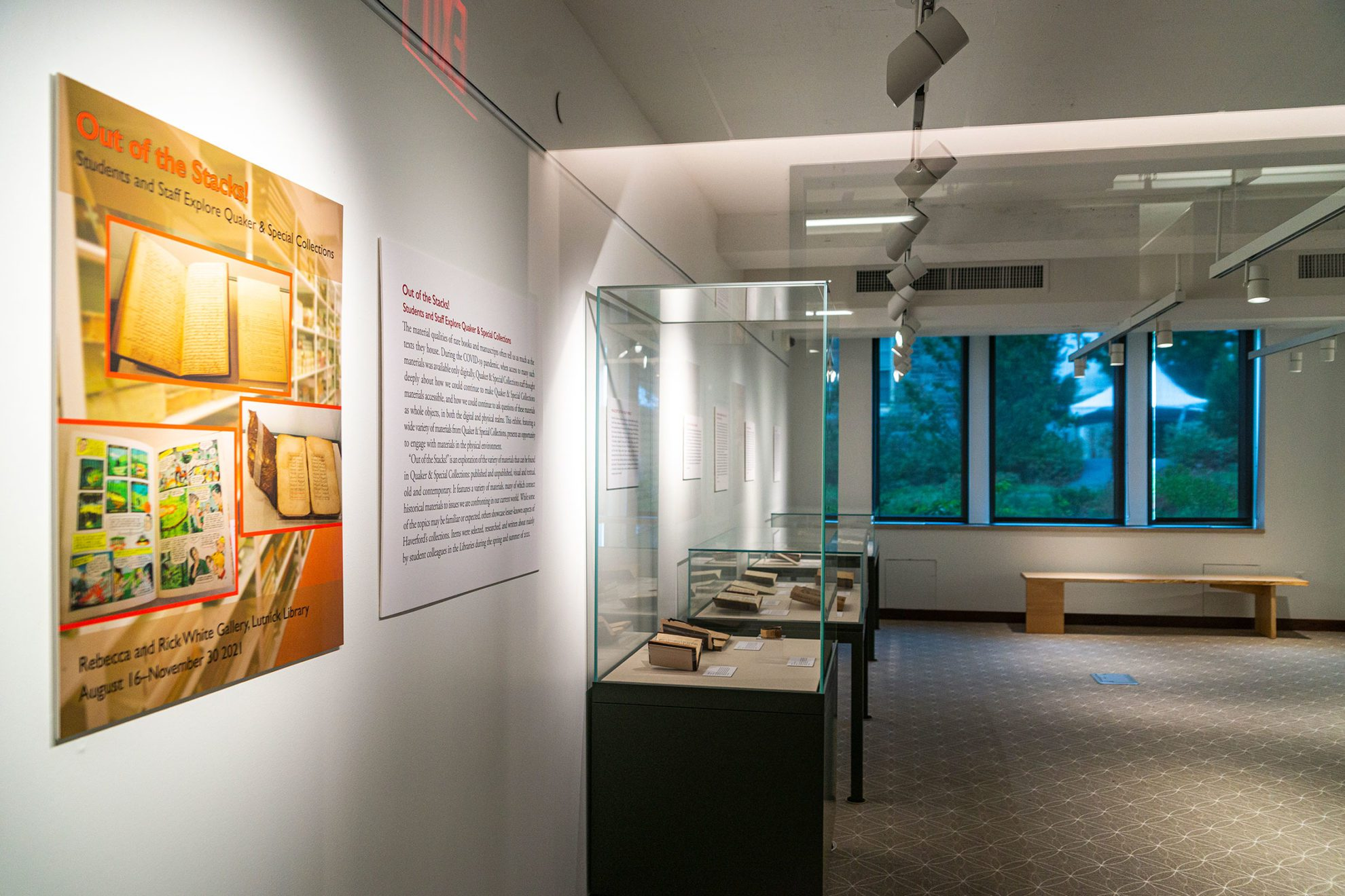 """The wall signage for """"Out of the Stacks"""" and several of the glass exhibition cases filled with items from Special Collections."""